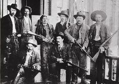 """""""The most dangerous outlaw in Indian Territory,"""" Ned Christie was shot to death in 1892. His body was placed on a board (back row, third from left), while U.S. deputy marshals posed with their """"prize"""" and their 1873 and 1886 Winchester lever-action rifles—along with one trapdoor Springfield single-shot rifle. Christie holds his .44-40, 1873 Winchester for the last tim"""