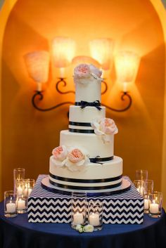 elegant and modern white wedding cake with navy ribbons, fresh flowers & chevron cake stand