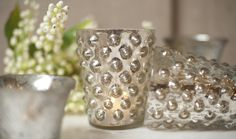 COLOR's Mercury Glass Pebble Votive $16.  DIY something similar for bathroom storage with glass pebbles and spray paint?