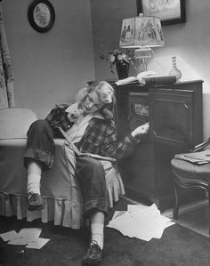 vintage vibe Teenager Pat Woodruff pondering homework while listening to radio in living room. Location: US Date taken: 1944 Photographer: Nina Leen