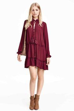 Volantjurk: Een korte, rechte jurk met volants. De jurk heeft drawstrings met een kwastje aan het uiteinde in de halsopening en in de taille, een sluiting met beklede knopen boven en lange mouwen met blind elastiek onderaan. Ongevoerd.