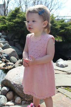 This classic styled dress features several different stitches that remind me of the waterlilies that bloom in my pond. The dress is knit in the round from the bottom up and has a two button closure in the back. Just seam at the shoulders and you are done! A great project to learn a few new texture stitches.A sweet little dress for your little girl, this dress works up beautifully in any sport weight yarn with good stitch definition. I suggest a cotton blend such as the KnitPicks Comfy Sport…