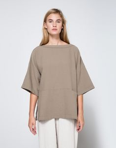 From Black Crane, a casual textured top in Cement. Boat neckline. Dropped shoulder. Three-quarter length sleeves. Small front pocket. Dropped waist. Side slits. Stitch detailing throughout.    • Thick crinkle cotton • 100% cotton • Machine wash cold,