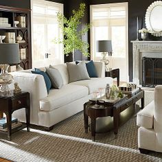 A clean, crisp living space with a modern fireplace. #white #couch #teal #grey