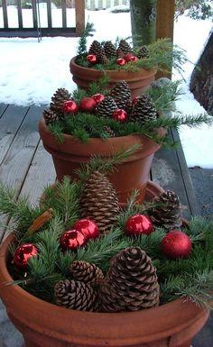 Inspiration rustique pour décorer le jardin à l'occasion des fêtes de Noël. Une idée de décoration extérieure à fabriquer rapidement et avec un tout petit budget (placer des pommes de pin, des boules de Noël et des branches dans des pots)