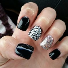 Black and glittery silver acrylic fake nails with two accent nails. One being silver glitter and the other being a black shellac base with silver gems/rhinestones glued onto it