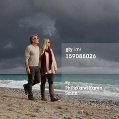 Stock Photo : Couple walk along beach after storm clouds pass
