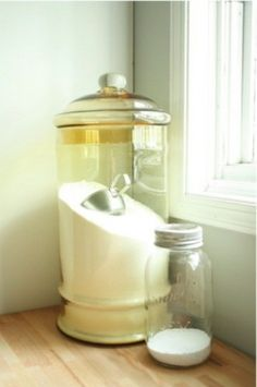 Lovely glass canister holds laundry detergent, keeping the laundry room looking cool.