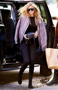 Gigi Hadid wears a black top, bomber jacket, skinny jeans, and thigh-high boots