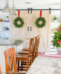 Our Christmas kitchen featuring hanging boxwood wreaths, barn doors, fresh greens and holly berry, boxwood Christmas tree and red ribbon, striped hand towels from HomeGoods (sponsored) and ornaments as accents.