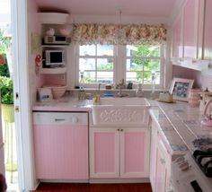 I actually really like the way this kitchen is set up. If it were mint green instead of pink it would be perfect. Also! Check out the outside...gardeny and green :) It's like a happy little cottage.