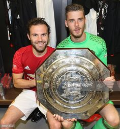 Juan Mata and David de Gea of Manchester United pose with the Community Shield trophy in the dressing room after the FA Community…