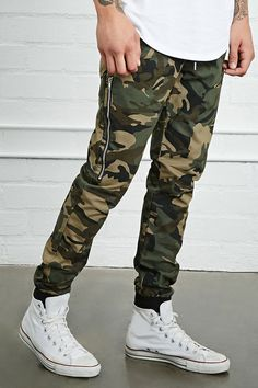 Style Deals - A pair of woven joggers featuring an allover camo print, an elasticized ribbed knit drawstring waist, side slip pockets, twin high-polish zippered side pockets, back baste-stitched welt pockets, and elasticized ribbed ankles.