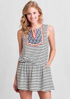 We love this adorable black and white striped dress complete with a V-cut tunic neckline with orange, cream, and blue colored embroidery at the bust.