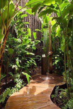 Un hombre alto, pantallas de privacidad valla de bambú contiguos en esta hermosa ducha al aire libre, aislada.  El exuberante paisaje añade privacidad adicional frente a las posibles miradas indiscretas.