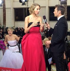 New fav photo! Taylor photobombed by Jennifer Lawrence during an interview with Ran Seacrest