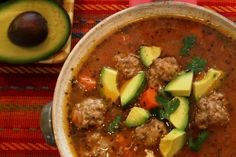 Albondigas Soup (Mexican Meatballs,Rice & Veggies) - Albondigas soup is a Mexican soup with delicious meat balls, carrots, rice, and a slightly spicy tomato based broth. It has some great mexican seasonings…Mexican Oregano, Cumin, and some salsa for excellent flavor! This is one of our family favorites, and is best garnished with chopped avocado and cilantro on top.
