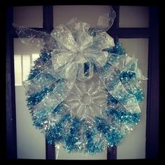 Winter snowflake wreath made from a dollar store pool noodle, garland, ornament, and bow.
