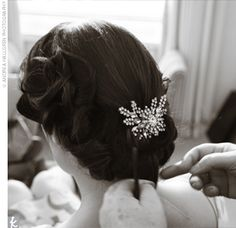 Alice wore her hair in a traditional, glamorous style with curled sides pulled into a low bun and fastened with a vintage-style crystal brooch.