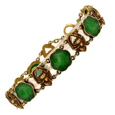 """Art Nouveau Jadeite Gold Link Bracelet. This antique Art Nouveau bracelet is crafted in 14K gold and weighs 20.00 grams and measures 7"""" long and 12mm wide. This naturalistically inspired bracelet of unique delicacy incorporates 6 artfully carved jadeite flowers within gold frames of scalloped borders, complemented by 6 alternately juxtaposed relief profiles depicting enchanting flowers. The 12 gold and jadeite links are adjoined by means of delicate gold ringlets."""