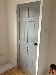 Grey door, black knob, black hinges, white surround.