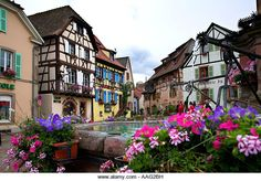 Town square with fountain in the picturesque town of Eggisheim in the Alsace region of France. - Stock Image
