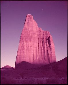 The Steeple in the South Desert- Capital Reef Nat'l Park, Utah. Late light catches the warm tints on the Entrada Sandstone steeple with a young moon looking over its shoulder. Compliment to nearby cathedral-like cliffs, this formation is most striking. [Caption by Josef Muench] :: Colorado Plateau Archives