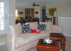 Contemporary upholstered sofa and antique Chinese tables with folding screen in rear