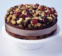 If you're not keen on icing and marzipan, bake a crown of toasted nuts, seeds and juicy cherries onto your cake instead. From BBC Good Food Christmas Cake Decorations, Christmas Cakes, Christmas Goodies, Christmas Fruitcake, Christmas Recipes, Boiled Fruit Cake, Cake Decorated With Fruit, Cake Board, Cake Toppers