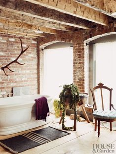 A freestanding tub sits on antique wide-panel floors. #HouseandGarden