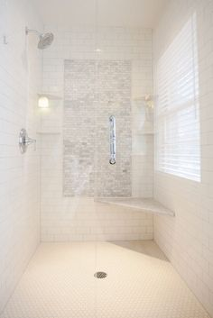 Stunning walk-in shower with a subway tiled interior and mini marble brick tiled accent panel flanked by corner shelves with rainfall shower head to the left and marble corner seat to the right over white mini hex tiled floors.