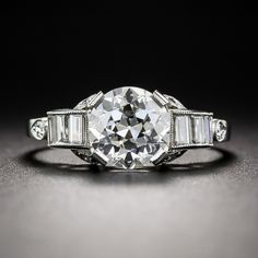 By the historic Chicago based house of fine jewels - C.D. Peacock (est. 1837), comes this seriously stunning, original Art Deco sparkler, masterfully hand fabricated in platinum - circa 1920s-30s. A gorgeous, bright white and brilliant European-cut diamond, weighing just one point shy of 1.50 carats, sizzles between rolled scrolls of glitter baguette diamonds, accented on three sides by tiny, fancy set twinklers. What's not to love? Currently ring size 6.
