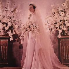 In a bower of flowers, Princess Alice of Gloucester (1901-2004) on her wedding day in 1935. A Scottish aristocrat with a triple-barrelled sir name, she married Prince Henry, third son of George V.  Her deluxe gown in pale pearl-pink satin was designed by Norman Hartnell. Photograph - Madame Yevonde.
