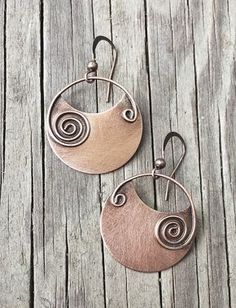 Copper earrings with copper spirals. I created these earrings by cutting copper discs and soldering on a hand-formed copper spiral made of square copper wire. I then oxidized and brushed for a rustic,