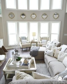 Kelley Nan (@kelleynan) • Instagram photos White Gray and Neutral 2 two story great room living room with quatrefoil mirrors between bow of windows | pottery barn thatcher wingback chairs | la-z-boy sectional sofa | zgallerie palais collection coffee table with oversized tray | living room ideas and inspiration KELLEYNAN.com