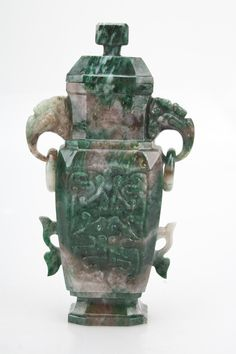Description: Chinese hard stone carved vase, the vase is in a striated green stone and has relief decoration on the body and zoomorphic ring handles.  item's measurements: Height: 15,5 cm Width / Diameter: 8,7 cm Depth: 4,1 cm  Item Date: 20th century.