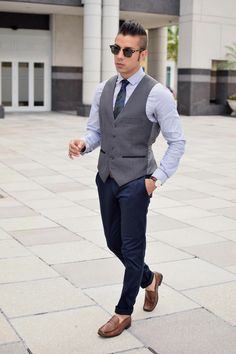 Tap into refined, elegant style with a dark grey waistcoat and navy chinos. A pair of brown leather loafers brings the dressed-down touch to the ensemble.  Shop this look for $294:  http://lookastic.com/men/looks/chinos-and-tie-and-loafers-and-sunglasses-and-dress-shirt-and-tie-and-waistcoat-and-loafers/4079  — Navy Chinos  — Navy Camouflage Tie  — Brown Leather Loafers  — Black Sunglasses  — Light Blue Dress Shirt  — Navy Camouflage Tie  — Charcoal Waistcoat  — Brown Leather Loafers