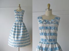 vintage 1950s cotton dress  white background with  blue, purple and black print  that has a hand-drawn style to it  back center metal zipper  wide