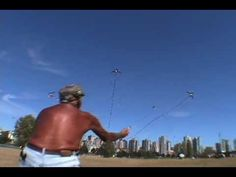 """""""Romancing The Wind"""" - Ray Bethell - The guy flying the 3 kites is in his 80s, and he's from Canada .. He comes to the Washington State International Kite Festival every year. His skin is like leather as he normally flies with his shirt off. He is deaf, so when he flies we hold our hands up and wave them for applause. He flies 2 with his hands and the 3rd one is attached to his waist. Enjoy!"""
