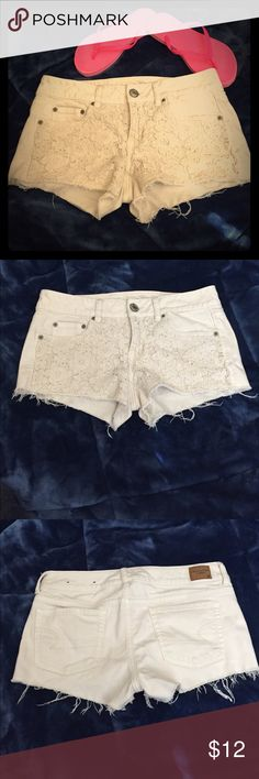 Size 4 American Eagle Lace Denim Shorts These are a pair of girly and cute American Eagle lace shorts. They are a slightly off white color with a floral lace design on the front. Other than the decorative fraying, there are no flaws! American Eagle Outfitters Shorts Jean Shorts