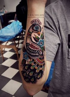 old school style peacock watercolor tattoo on forearm - bird, flowers, leaves