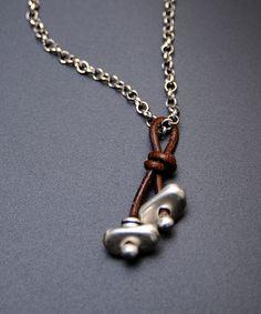 Colgante de cuero con entre piezas de zamak.  Sencillo y muy estiloso, con cadena corta, como gargantilla.