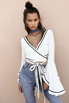 The effortlessly stylish Monochrome Wrap Top is made from a lightweight, textured fabric in an off white hue. It is a cropped, wrap style top and features black accents, a cross over V neckline and full length sleeves with flared cuffs. Complete the look with distressed high waisted denim shorts and slides! By Sabo Skirt.