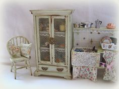 A lovely very old and shabby looking Larder cuboard/pantry or pie safe painted in a very pale green and distressed to make it look as old and worn as possible The door has metal mesh and a oriental style handles