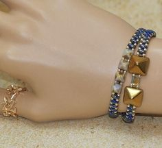 This Blue Pyramid Superduo Bracelet is feminine, simple and stunning. The Pyramid are surrounded by deep blue luster superduos, and shiny gold plated seed beads and finished with a lobster claw clasp.
