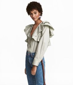 Light green. Straight-cut, V-neck blouse in woven cotton fabric with large ruffles at top and concealed buttons at front. Long, wide sleeves with pleats and