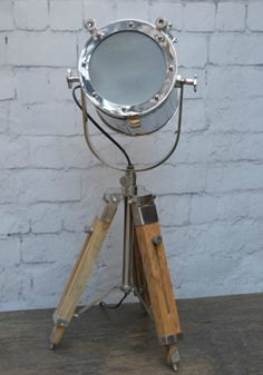 Nautical Searchlight Table Lamp        Inspired by naval searchlights, and often referred to as photographers lamp, patrol lamp, hollywood style lamp, this vintage lamp will look bold with any style of interior. The telescopic legs are fully adjustable making it easy to adjust the height of the lamp. is the head which can be pointed anywhere in the room.        Dimensions:      Height 62 cm (up to 75cm with legs extended)  Width 23cm  depth 23cm  easy to reach on/off switch  Weight…
