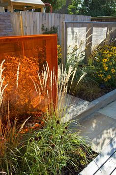 The second, central area of the garden is planted with low maintenance architectural plants.  Four screens of various dimensions emerge from the planting and help to obscure the rear of the space from view.  Each screen features a different material: wooden panelling, textured stone tiles, stainless steel mesh and orange Perspex.   #orange #mesh #screens #gardendesign