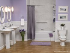 Light purple linens pair well with a white alcove bathtub, lavender painted walls, laminate shower wall covering and light hardwood flooring.
