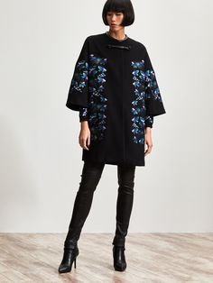 One of our iconic shapes, this easy A-line coat has elegant symmetrical embroidery, putting winter florals at the heart of the collection. The kaleidoscope orchid pattern is embroidered, with space dye print on top. The round, micro mandarin collar has a leather trim and the coat fastens with a beautiful leather frog button. The coat is knee-length, with flared sleeves.   Colors: Black      Ref: 1RA46R2